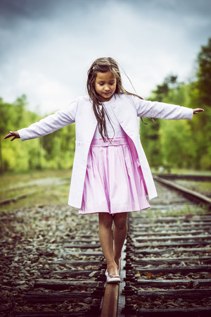 railroad track: little thai girl balancing on a railroad track, vintage effect added Stock Photo