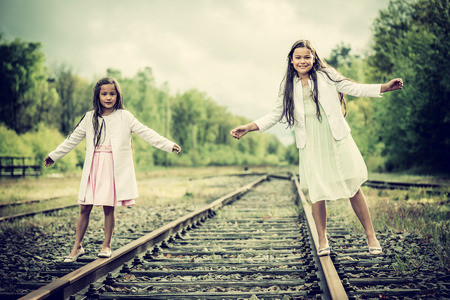 railroad track: two sisters balancing on a railroad track, vintage effect added