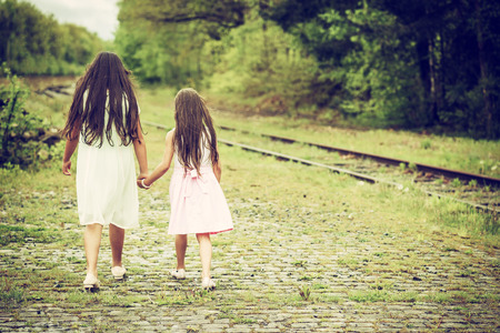 shot from behind: two sisters walking next to railroad track, shot from behind