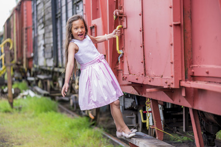freight train: litttle thai girl hanging on the side of a freight train like a blind passenger Stock Photo