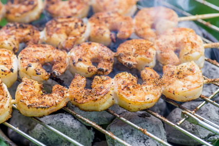 spiced: spiced schrimp skewers being grilled on a barbecue