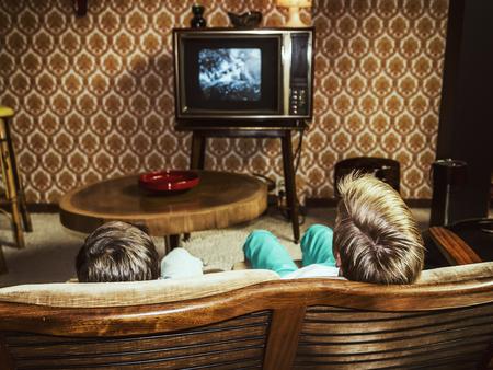 viendo television: dos niños que miran la televisión en su casa en el estilo de los años 50, dispararon desde atrás