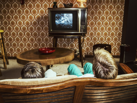 two boys watching television at home in 50s style, shot from behind