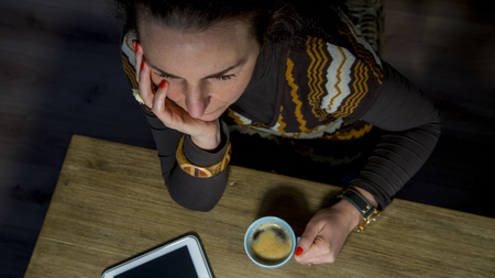 high angle view: high angle view of woman with coffee and tablet