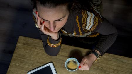 high angle: high angle view of woman with coffee and tablet