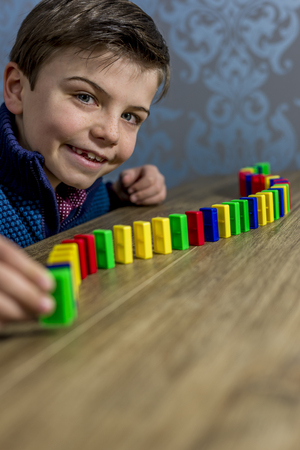 by placing: boy placing domino pieces on a table, shallow depth of field