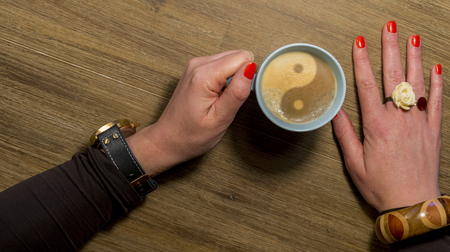 womans hand holding cup of coffee with yin yang sign Stock Photo