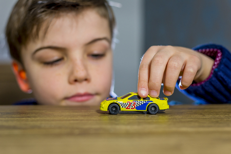 nascar: boy playing with toy car on a table, shallow depth of field
