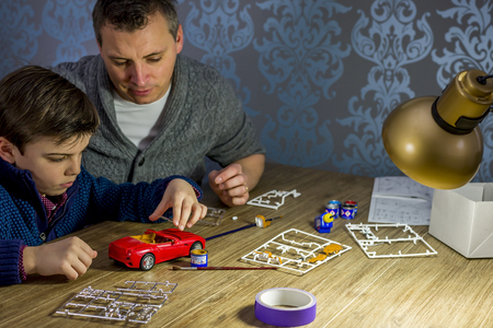 father and son building a model car, shallow depth of field