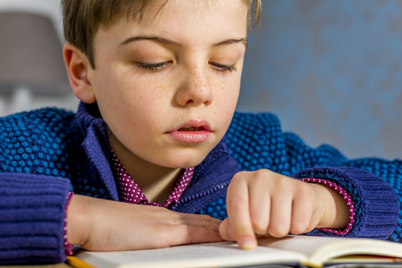 boy reading a book close up portrait
