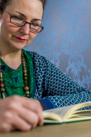 middle aged woman with glassen  reading a book Stock Photo