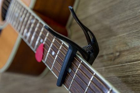 close up of a capo on an acoustic guitar