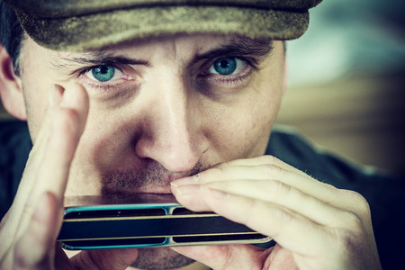 close up portrait of a man playing a harmonica