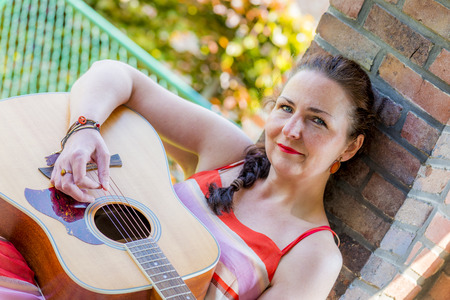 beautiful middle aged woman playing acoustic guitar Stock Photo