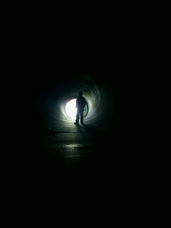 Construction worker standing in a big pipe