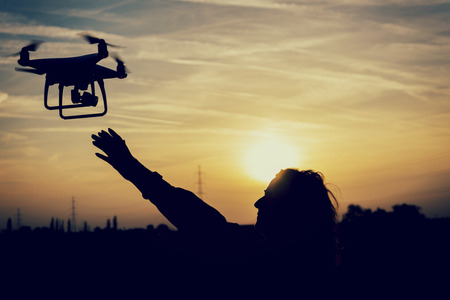 silhouette of a woman catching a drone