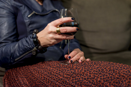 womans lap with glass of red wine