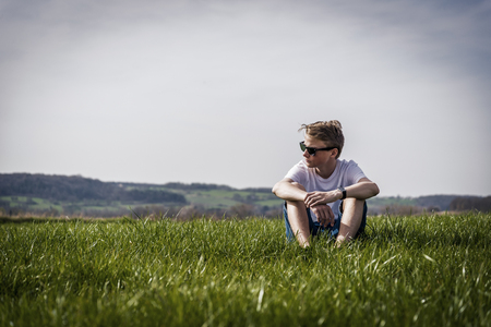cool looking boy sitting relax in a field Stock Photo