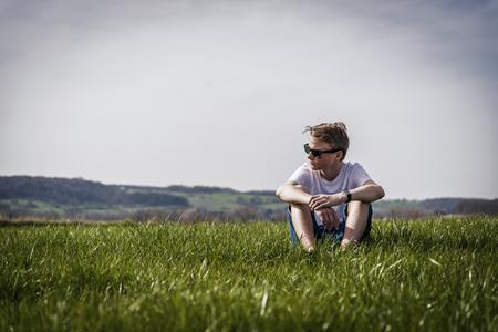 cool looking boy sitting relax in a field 版權商用圖片