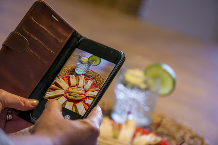 a woman using a smartphone to capture her meal for social media