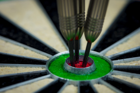 macroshot of three darts in the bulls eye of a dartboard  Stock Photo