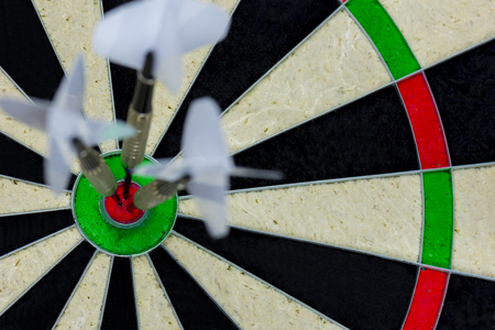 three darts thrown at the bulls eye of a dartboard