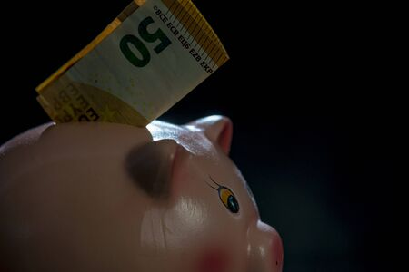 piggy bank on a black backgroud with fifty euro sticking out of his back Stock Photo