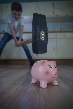 little boy swinging a big hammer towards a piggy bank. shallow depth of fiield. Stock Photo