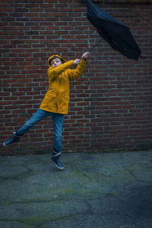 boy with umbrella blown away by a storm