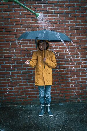 boy standing under an umbrella with a watering can above him for some fake rain Stock Photo