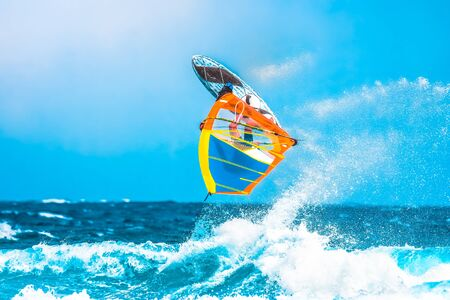 summer sports: windsurfer making an acrobatic jump in the waves and spray the seawater
