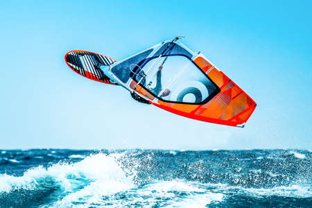 summer sports: windsurfer jumping in the waves Stock Photo