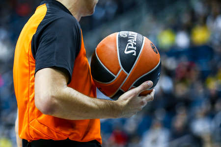 Berlin, Germany, October 04, 2019: a referee holds the official basket game ball during a Turkish Airlines EuroLeague match between Alba Berlin and Zenit St Petersburg at Mercedes Benz Arena