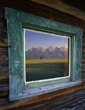 ranch house: The Teton Mountain Range reflecting in the window of a ranch house, located in Grand Teton National Park, Wyoming.