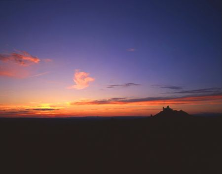 A butte silhouetted at sunset.
