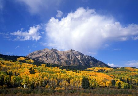 Mountains, aspen trees and clouds along the Kebler Pass Road, in the Gunnison National Forest of Colorado, photographed during the autumn season.