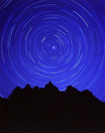 A circle of stars and silhouetted mountains.