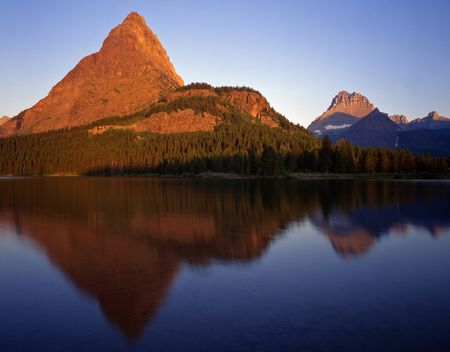 Mountains reflecting in Swiftcurrent Lake located in Glacier National Park, Montana, photographed in the early morning. Stock Photo