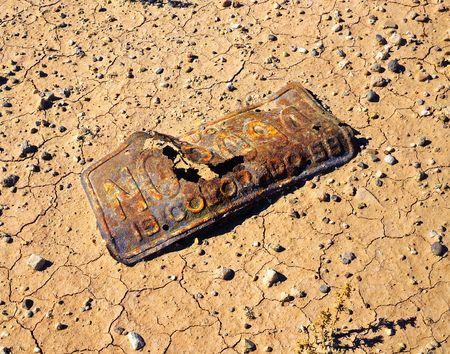 rusting: An old Colorado license plate rusting away in a desert in Utah.