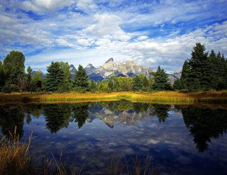 The Teton Range reflecting in the Snake River, at Schwabachers Landing, in Grand Teton National Park, Wyoming. Stock Photo