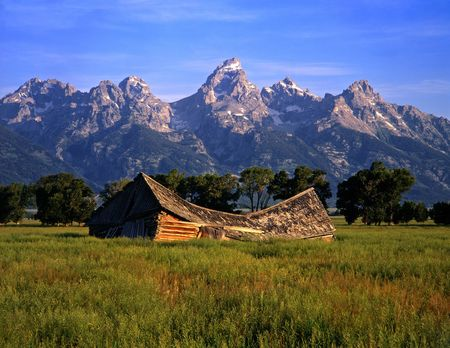 A barn, at the foot of the Teton Mountain Range, that is falling down.  Location, Grand Teton National Park, Wyoming.