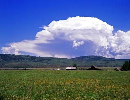teton: Un fienile e grandi nuvole in Grand Teton National Park, Wyoming.