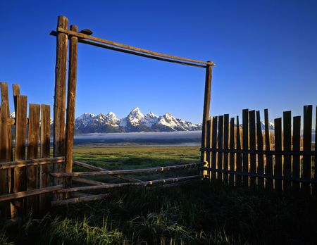 A fence, gate and the Teton Mountain Range, in Grand Teton National Park, Wyoming. Stock Photo
