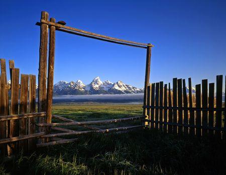 teton: Un recinto, cancello e la catena montuosa Teton, nel Grand Teton National Park, Wyoming.