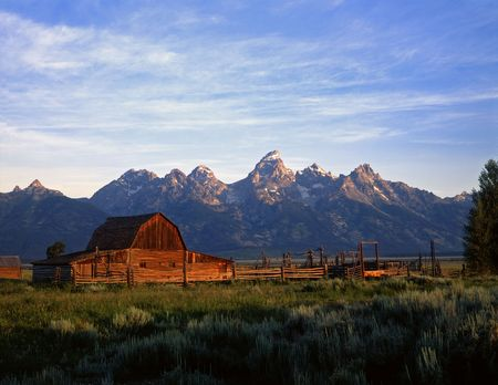 An old ranch and the Teton Mountain Range in Grand Teton National Park, Wyoming. LANG_EVOIMAGES