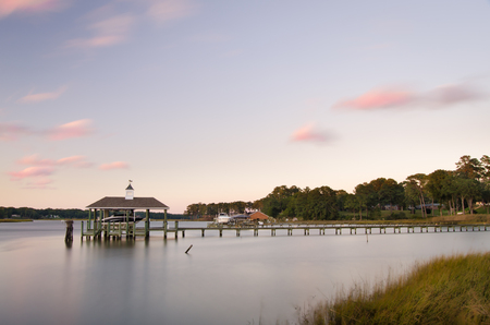 A boat dock juts out into the Pagan River in Smithfield, Virginia at dusk. Stock Photo - 110676391