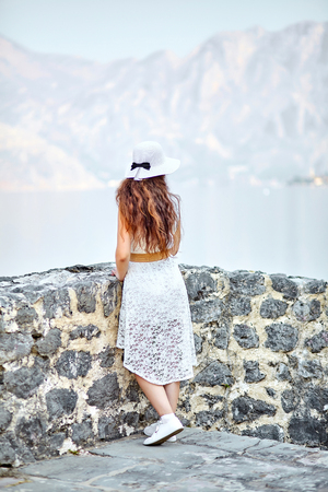 A young girl in a white dress and hat admires a beautiful view of the sea and mountains