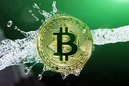 Golden bitcoin and water splash on dark background. Money laundering, enrichment and profit concept