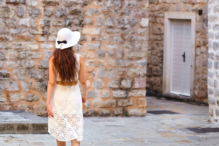 Young brown-haired woman in white hat and dress walking the narrow street of the old city Foto de archivo