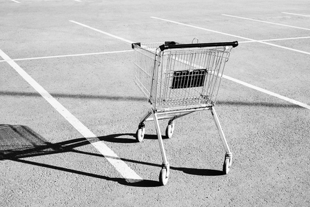Shopping cart in a store parking lot. Black and white